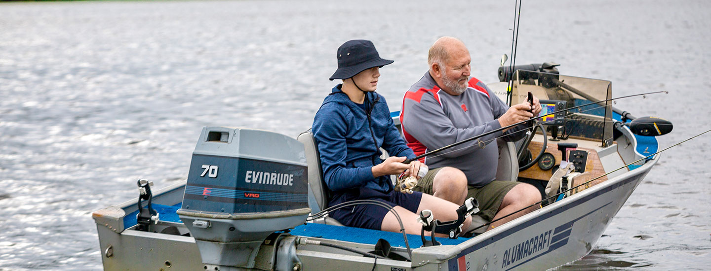 grandfather and grandson fishing in a boat