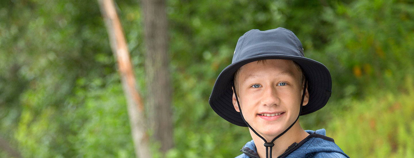young boy outdoors smiling
