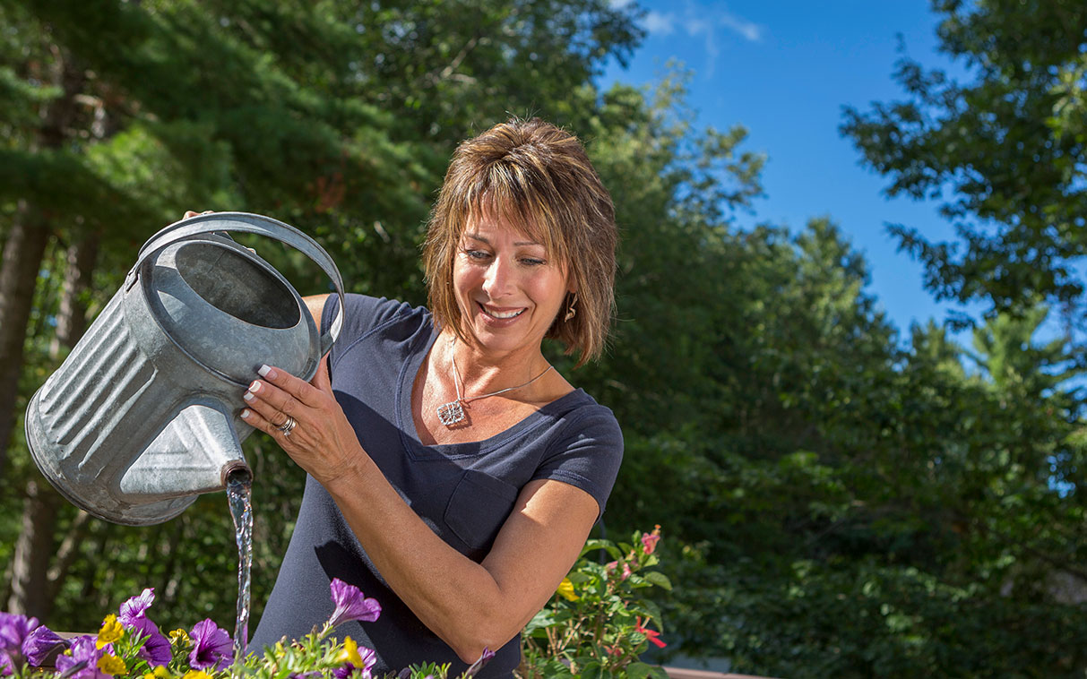 woman watering her outdoor garden