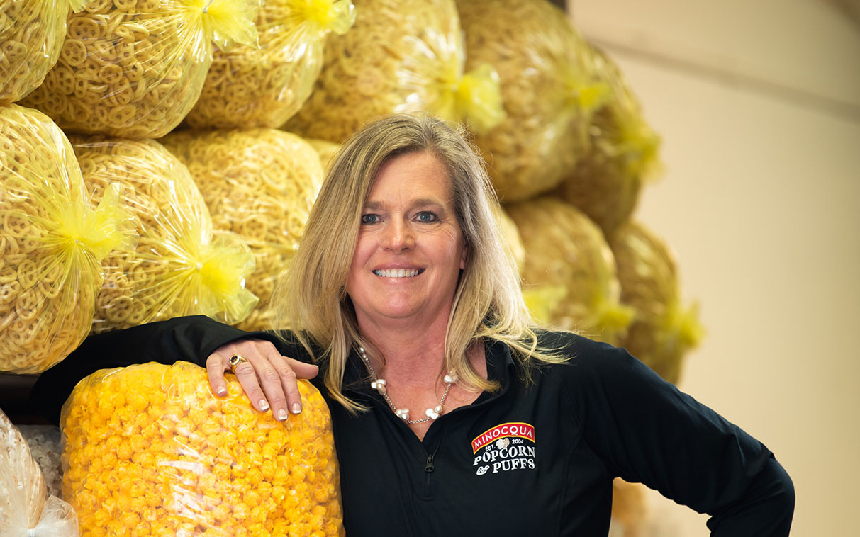 business owner of a popcorn business smiling with popcorn