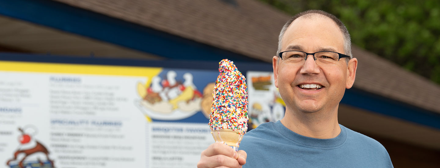 Ice cream shop owner holding an ice cream cone with sprinkles